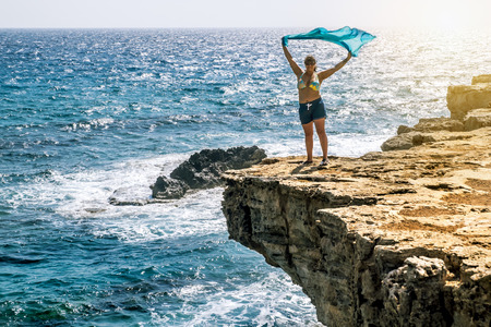 ledge: 25 may 2016.Cape Greco.Woman standing with waving in the wind with a handkerchief on the ledge of the cliff above the sea at Cape Greco . Cyprus.