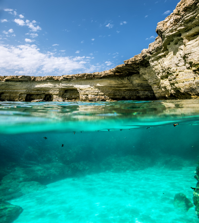 View of the cliffs and sea caves of Cape Greco from under the water and above the water.Cyprus Stok Fotoğraf