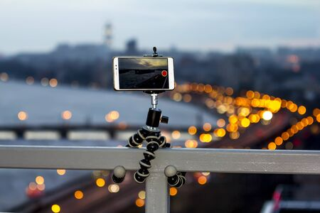 The smartphone is fixed on a tripod shooting a video with a colorful panorama of the city