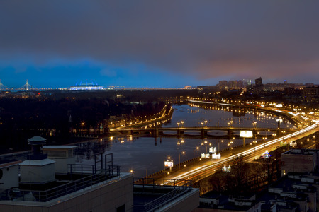 .The view from the heights on the river Neva and Ushakovskaya the Embankment in the evening lights in St. Petersburg. Stock Photo