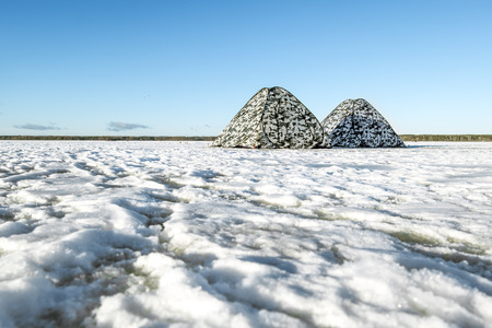 Tents fishermen stand on the frozen lake in winter Sunny day Stock Photo