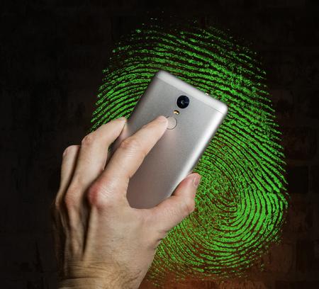 Finger touches the fingerprint scanner on the smartphone against a  fingerprint on brick wall Stock Photo