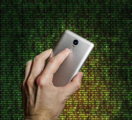 Finger touches the fingerprint scanner on the smartphone in the background of the digits of the matrix
