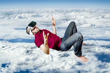 The man in glasses virtual reality flying on sky background Stock Photo