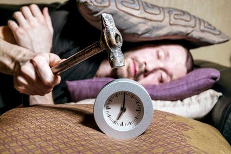 molesto: Un hombre despierto está tratando de romper el despertador molesto en la mañana
