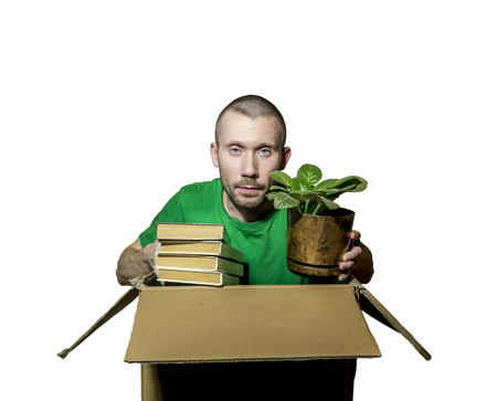 A man is sitting in a tight box and holds in his hands the books and flower on white background Stock Photo
