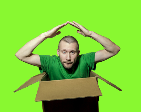 A man is sitting in a close box and folded his arms over his head isolated on green background