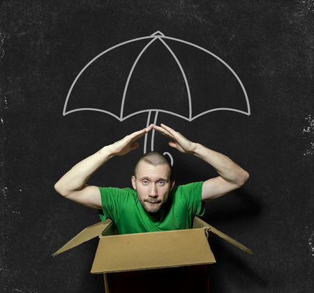 A man sits in a cramped box with your hands folded over your head on the background of the picture of the umbrella with chalk on blackboard