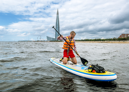 Saint-Petersburg.Russia.August 11, 2018.A man rowing on the sup board on the water of the Gulf of Finland opposite the skyscraper Lakhta in St. Petersburg 写真素材