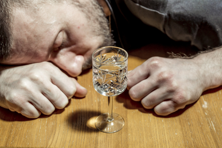 The man fell asleep drunk at the table in front of a glass of vodka before drinking