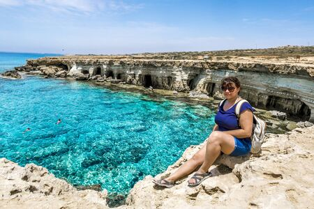 Cape Greco.Cyprus.21 may 2016.A girl sits on a ledge of rock above the sea at Cape Greco .