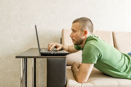 A man studies and works at home online on the Internet from a laptop while lying on the sofa Banco de Imagens