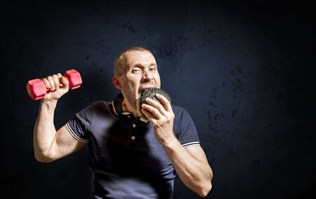 A hungry Man enjoys eating a black Burger and holding a dumbbell against a concrete wall. A man chooses between fast food and a healthy lifestyle.