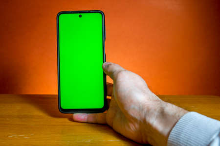 Man holds smartphone with green screen in hand on orange background