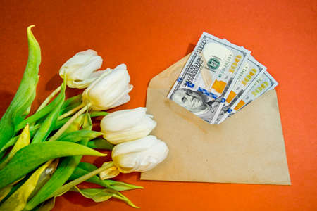 A bouquet of beautiful tulips and dollars in an envelope on an orange background top view. Background of Mother's Day, International Women's Day. Holiday, give a gift. Archivio Fotografico