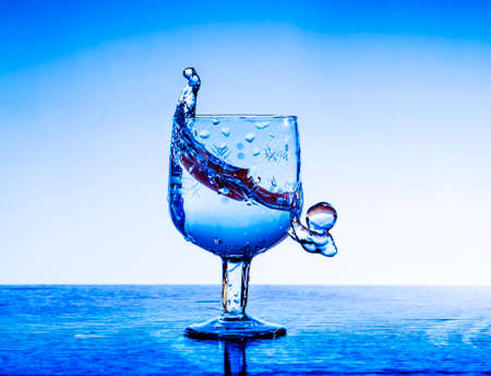 Splashes of fresh clear water in an exquisite crystal glass against a blue background