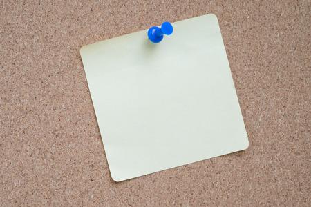 yellow pushpin: Yellow sticker pinned blue pushpin with cork background.