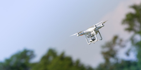 royalty free: Flying drone in action; photographed on a defocused background. Royalty free image, no logos in the photo. Stock Photo