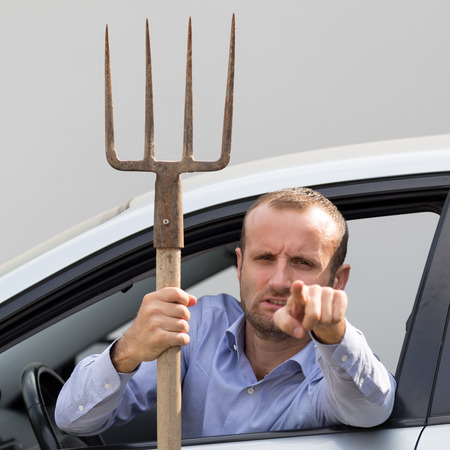 pitchfork: Aggressive and violent driver armed with a pitchfork Stock Photo