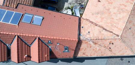 Aerial drone photo of a new roof with solar panels compared to old one without