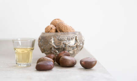 Walnuts, chestnuts and a golden liquor glass on a concrete surface