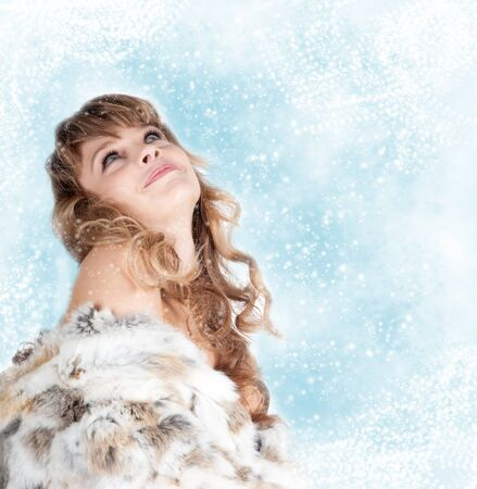young beautiful woman with long hairs in fur coat on snowy Christmas background photo