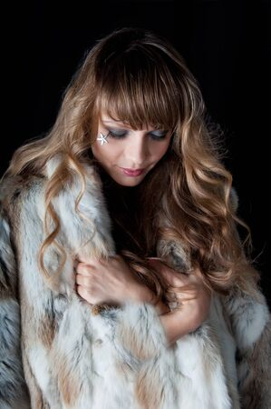 young beautiful woman with long hairs in fur coat isolated on black photo
