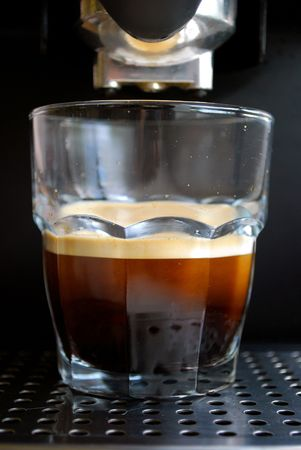 cortado: delicious espresso in a glass made by a espresso machine with a lot of crema