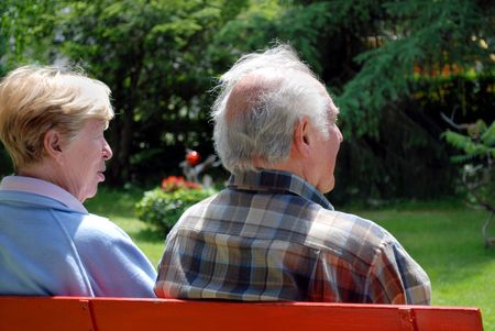 elderly happy couple sitting in a park on a bench photo