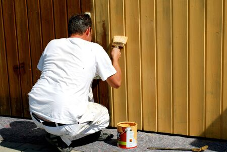 peintre en b�timent: house painter varnishing a garage door