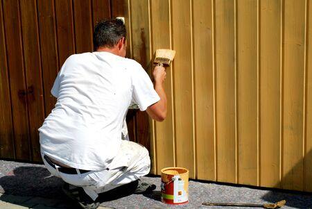 pintor de casas: pintor de brocha gorda barnizar una puerta de garaje Foto de archivo