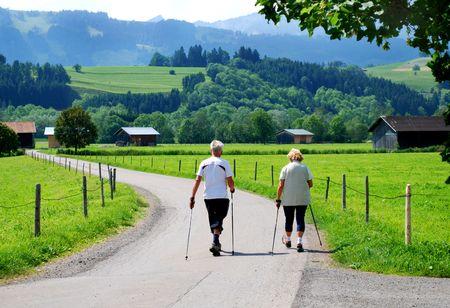 ancianos caminando: las personas de edad avanzada Nordic Walking en la Alemania Alpes de Baviera Foto de archivo