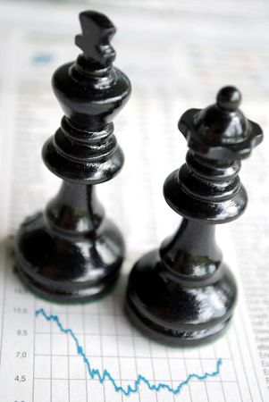 takeover: king and queen chessmen over the charts of quotation symbolizing the financial crisis