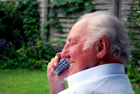 oma: happy elderly man phoning in the garden