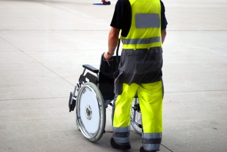 airport worker providing a wheelchair for disabled passengers Stock Photo - 5010939