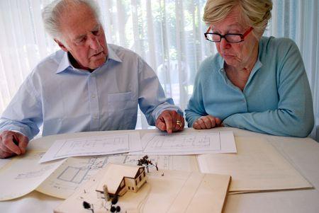 senior paar zoekt op een plattegrond en huis-model