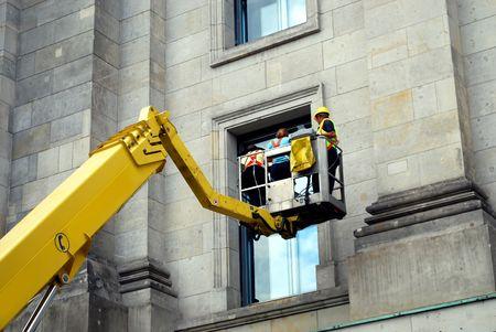 drie bouwvakkers in een hydraulische hellingbaan