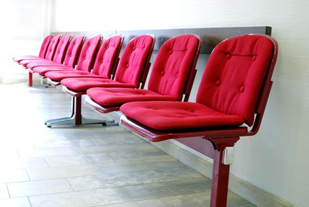 area: red seats in a row in a waiting room