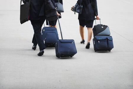 cabin crew women walking on the runway wih their trolleys photo