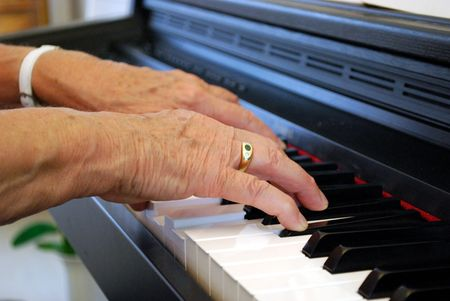 two hands of an elderly woman playing piano