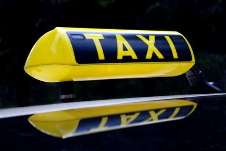 yellow neon taxi sign mirroring in the car roof Stock Photo