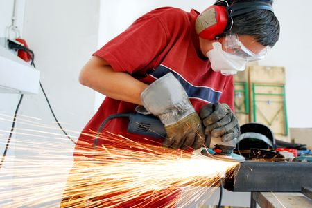 metal worker with a grinder and a lot of sparks Stock Photo