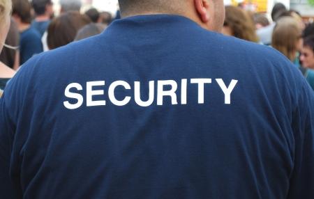 guarda de seguridad: parte trasera de un guardia de seguridad viendo una multitud de personas Foto de archivo