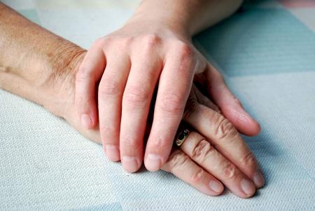 Nahaufnahmen der zwei Hände auf die Tabelle mit Tageslicht. Standard-Bild