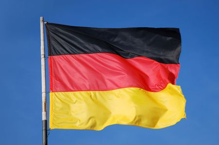 german flag waving in the wind in front of deep blue sky photo
