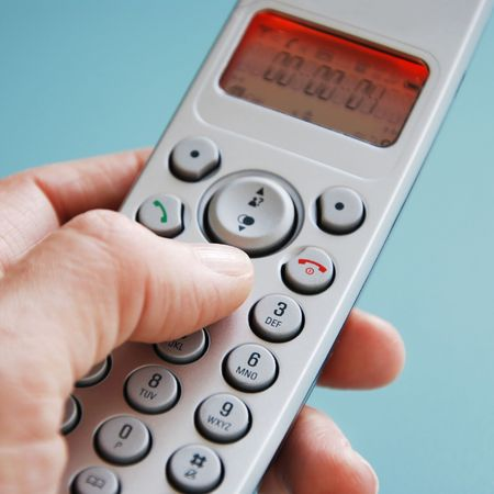 hand dialing the phone in front of green background photo