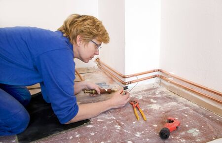female plumber soldering copper pipes on a construction site photo