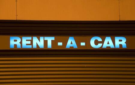 rental: signo de coche de alquiler iluminada de azul con fondo naranja  Foto de archivo