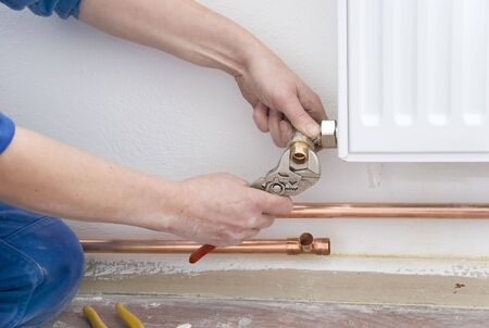 two hands of plumber with pliers and radiator photo