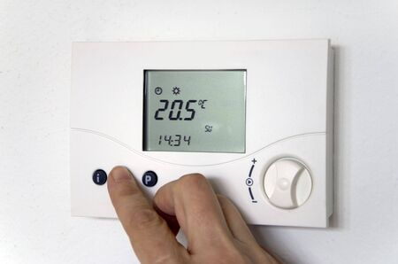 hand adjusting the thermostat of a heating system Standard-Bild